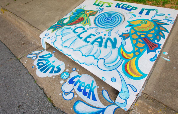 "Jeffi O'Kane's 2014 storm drain mural ""Let's Keep It Clean"" shows two fancy fish splashing about on the sidewalk under the words ""Let's Keep It Clean."" Under the drain are the words ""Drains to Creek""."