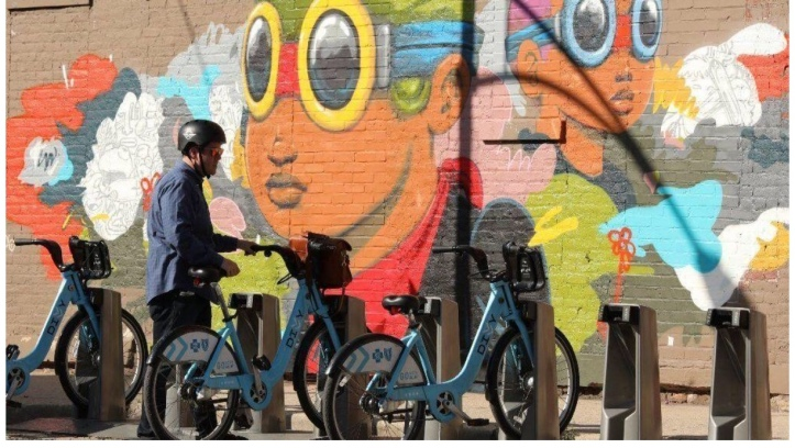 Hebru Brantley's mural, painted on a brick wall behind a bike share station, features his signature Flyboy character.