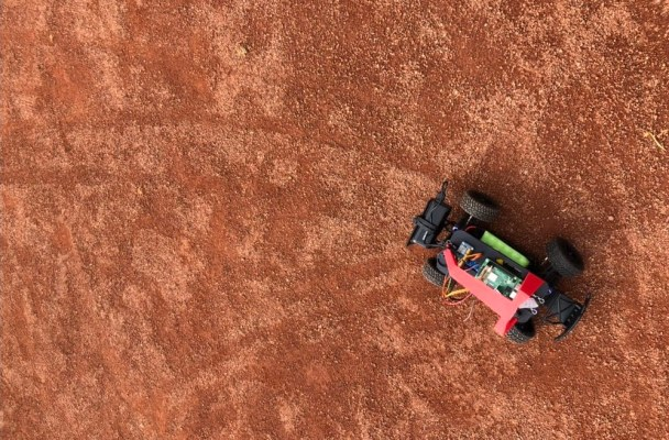 View of a remote control car from above, showing the tracks the car's tires have left on the bright orange dirt of a baseball field.