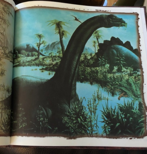 Photo of a page from a picture book that shows a sauropod wading chest-high in water.