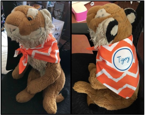 "A stuffed tiger sits in an office chair modeling his new orange and white tiger-striped bandana. Bandana reads ""Tigery""."