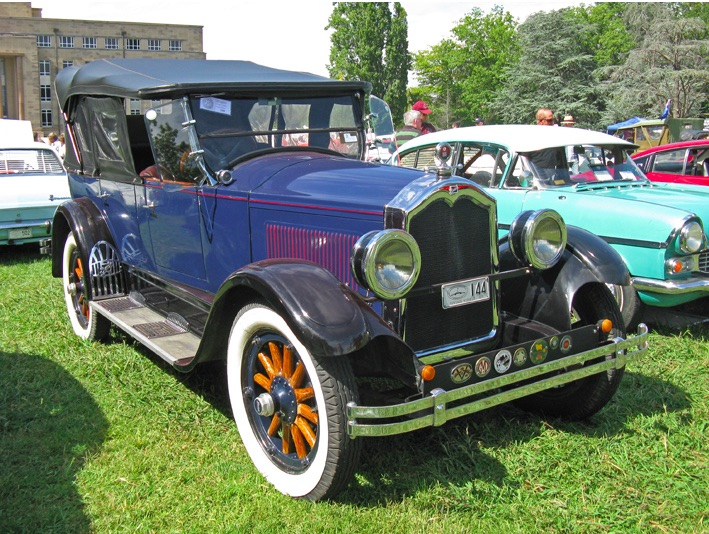 A restored 1927 Buick Touring car with a canvas top and side curtains that look to be made of clear vinyl.