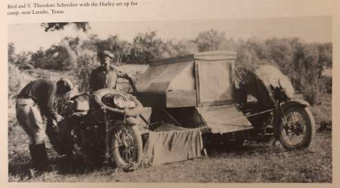 Black and white photo of two men. A canvas tent and a clothesline with a sheet hanging from it is stretched between two motorcycles which are absolutely loaded down with stuff, including several saddle bags and at least one spare tire. One of the men is fiddling with the motorcycle on the left. It's not clear to me which person is Bird.