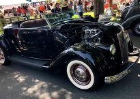 sleek black vintage convertible with white wall tires.