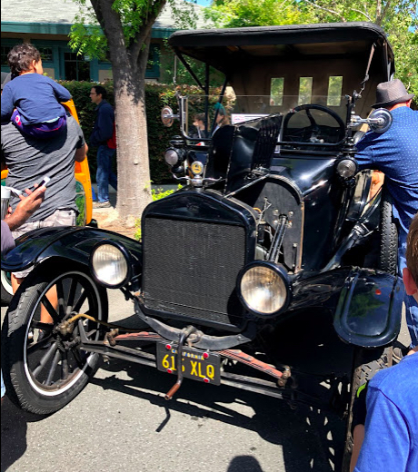 Model T, black, with open carriage and rusty hand crank coming out of its front engine.