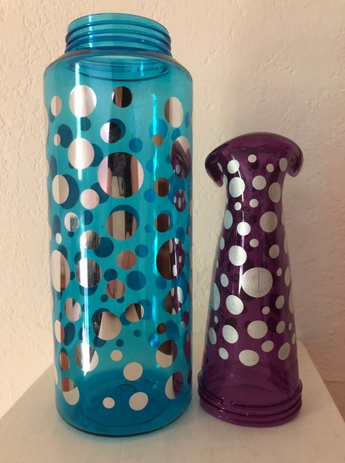 Two plastic water jugs. The one on the left is blue and still boasts its original straight sides and immense water capacity. The one on the right has shrunk in height, width, and has to sit on its top because its bottom has melted into a mushroom curve.