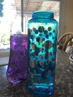 The purple bottle leaning against the blue bottle. The blue bottle is barely a quarter full.
