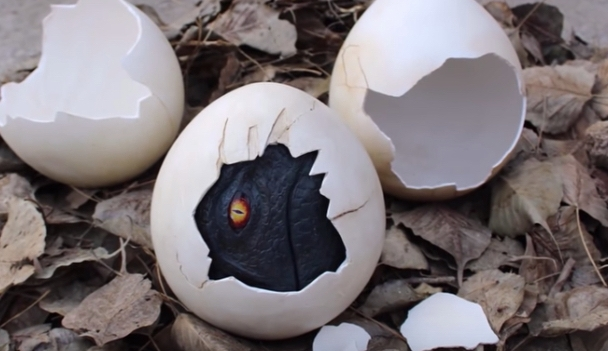 A dinosaur eye peers out from a partially cracked handmade dinosaur egg.