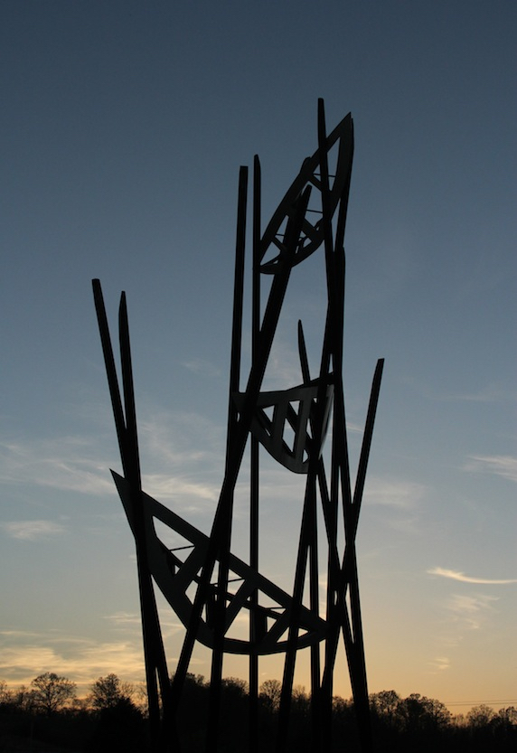 The sculpture resembles a series of three open work canoes suspended at various heights on a network of angled poles. The blues, greys, and orangey-pinks of the evening sky show through the sculpture.