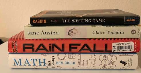 A pile of four books: The Westing Game by Ellen Raskin, Jane Austen by Claire Tomalin, Rainfall by Barry Eisler, and Math with Bad Drawings by Ben Orlin