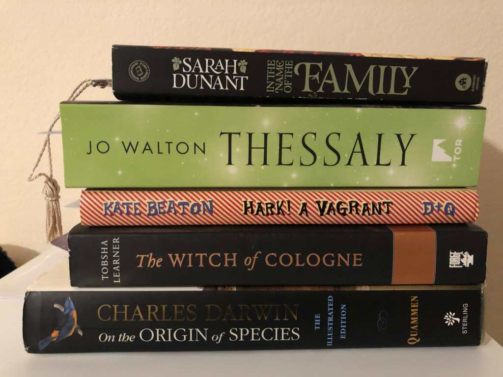 A pile of five books: The Illustrated Edition of Charles Darwin's On the Origin of the Species by David Quammen, The Witch of Cologne by Tobsha Learner, Hark! a Vagrant by Kate Beaton, Thessaly by Jo Walton, and In the Name of the Family by Sarah Dunant.