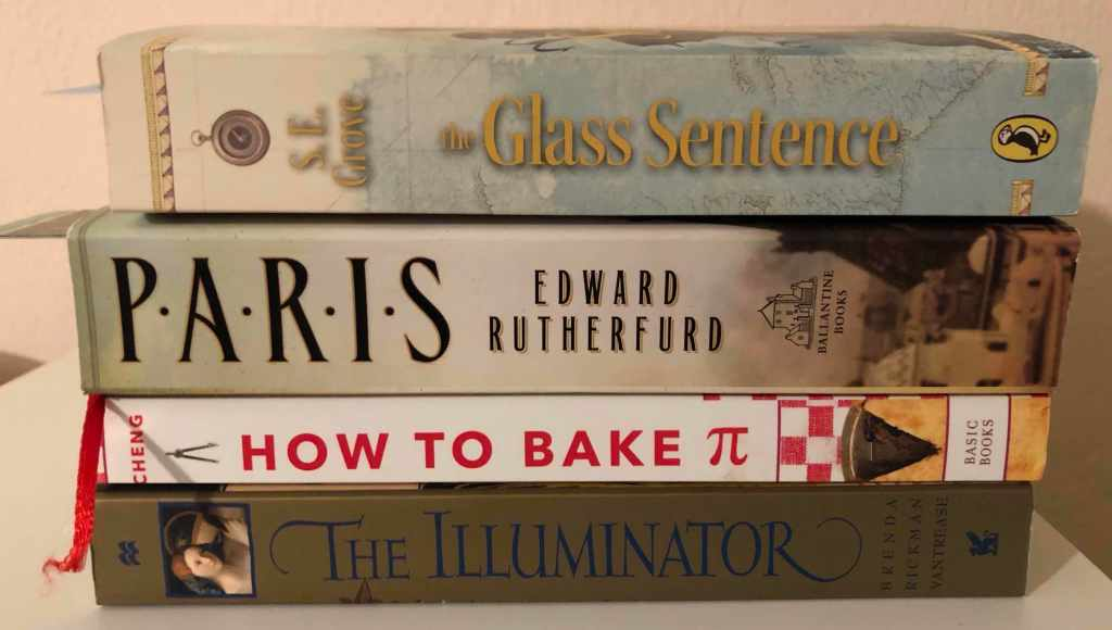 A stack of four more books: The Glass Sentence by S.E. Grove, Paris by Edward Rutherford, How to Bake Pi by Eugenia Cheng, and The Illuminator by Brenda Rickman Vantrease.