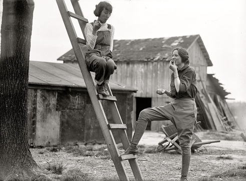 Black and white photo of two women in coveralls, on a farm, eating something apple-sized and round.