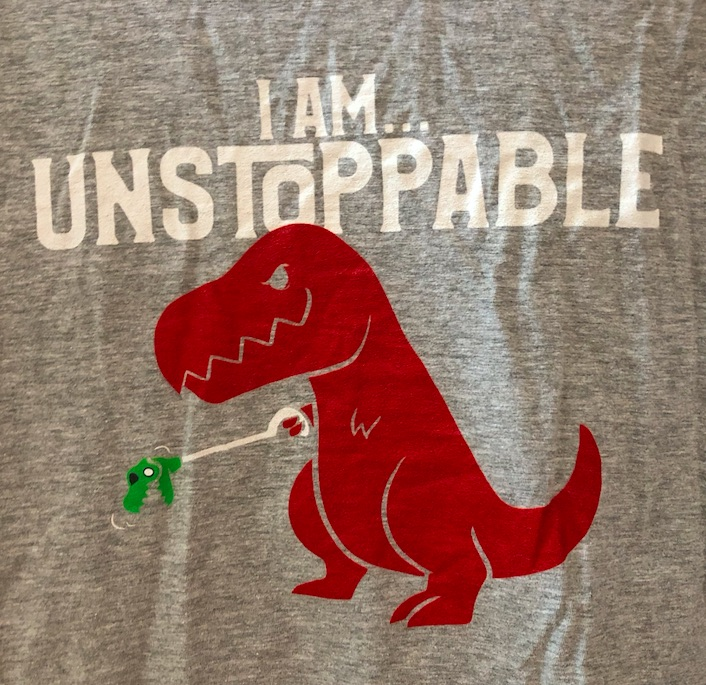 "Grey t-shirt with the words ""I am unstoppable"" above a T. Rex holding one of those mini T. rex grabby toys."