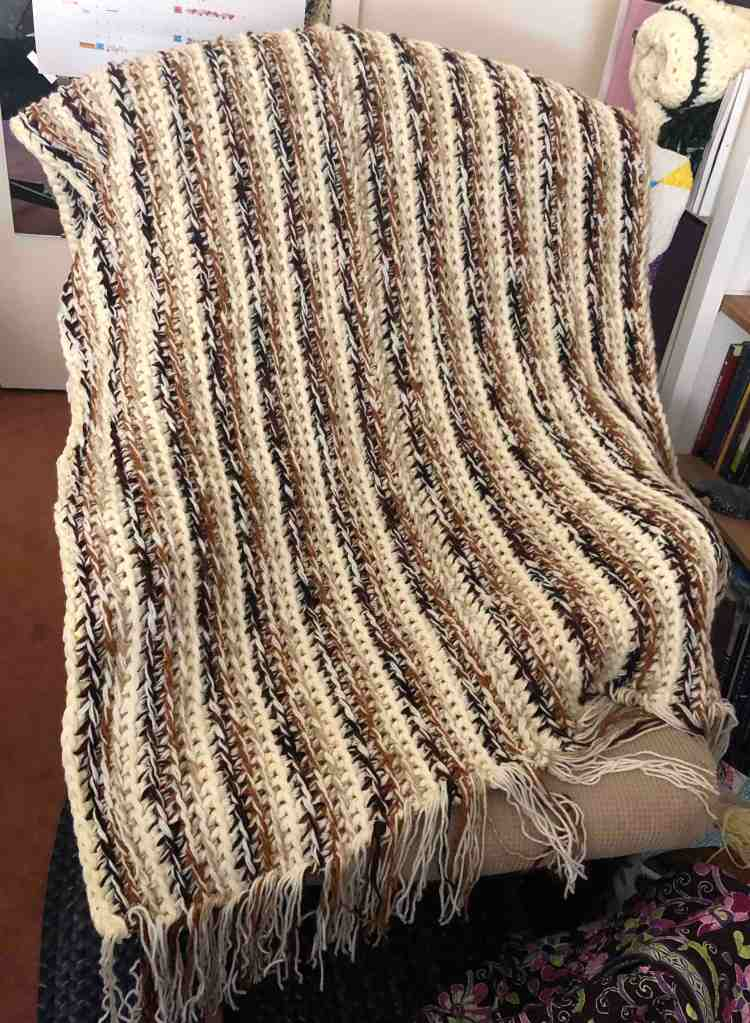 Photo shows a crocheted striped blanket draped across a rocking chair. The blanket is striped and crocheted in cream, light brown, rusty brown, and dark brown yarns.