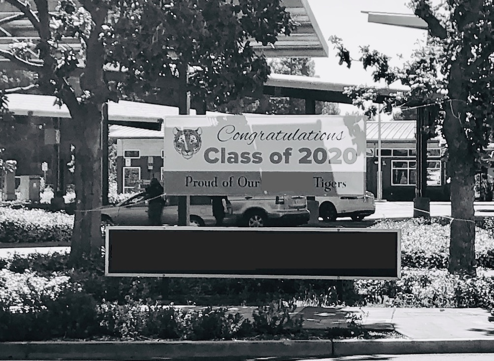 "Black and white photo of a banner posted in front of a middle school. Banner reads: ""Congratulations Class of 2020: Proud of our Tigers!"""