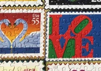 close-up of two stamps from the Love Stamp Puzzle. One shows a pair of swans in profile against a sunset (the swan's necks make a heart). The other shows the LOVE sculpture American artist Robert Indiana which has the letters L and O mounted on top of the V and E.