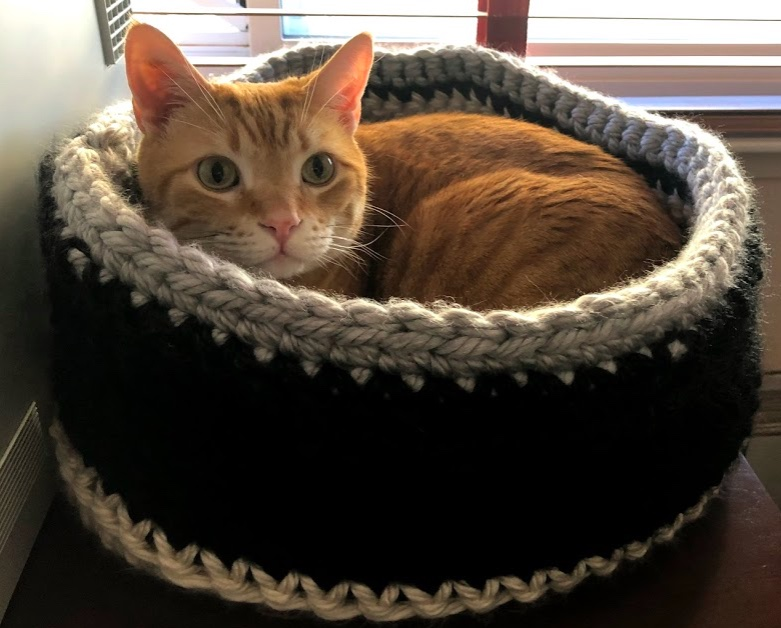 Orange cat nestled in a black, grey, and cream cat bed crocheted out of insanely bulky yarn.