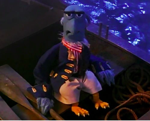 Sam the Eagle dressed as a sailor and seated in a row boat.