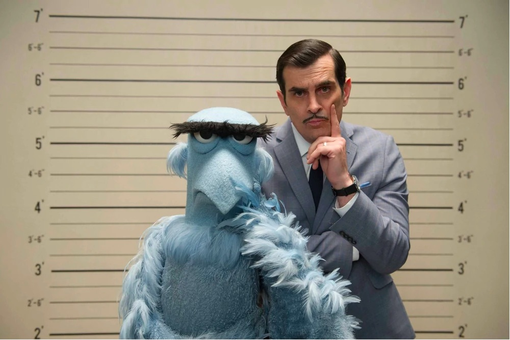 Sam and Jean Pierre Napoleon pose in front of a suspect height wall chart in this still from Muppets Most Wanted.
