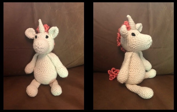 In this collection of two pictures, the unicorn sits on my leather couch posing from the front and from the side. He's crocheted out of cream colored yarn, with a cream colored horn, pink mane and pink tail. His eyes are made with black yarn.