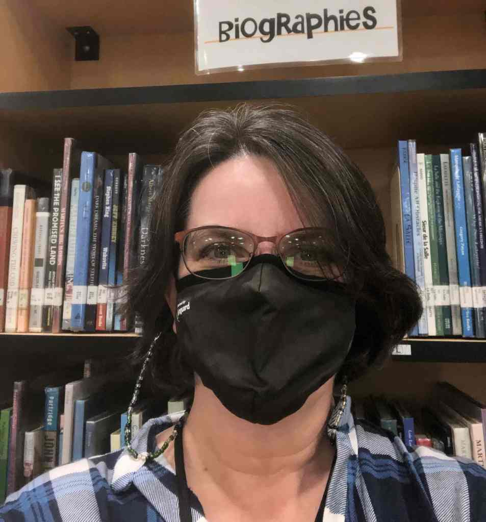 Me, with short hair and mask, standing in front of one of the biography stacks at the middle school library.